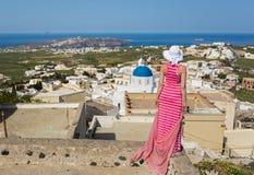 Donna in un vestito lungo, guardare isola Santorini, la Grecia immagini stock libere da diritti