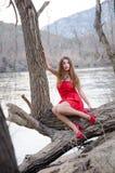 Donna in un vestito rosso audace come un piccolo cappuccio di guida rosso immagine stock