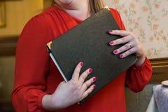 Donna in un vestito rosso che tiene una fine disponibila del menu su fotografie stock