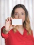 Donna in una camicia rossa che sostiene un biglietto da visita in bianco Fotografie Stock