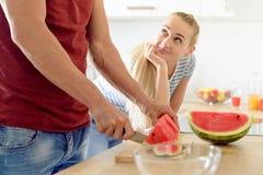 donna in una cucina che mangia anguria rossa e che esamina il suo marito, coppia nella loro grande cucina bianca contemporanea immagini stock libere da diritti