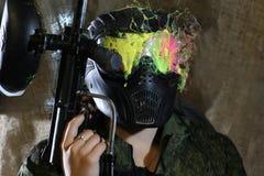 Donna in una maschera che gioca un paintball pericoloso Immagine Stock Libera da Diritti