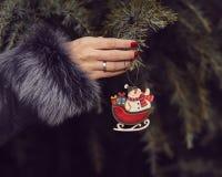 Donna in una pelliccia che decora un albero di Natale fotografia stock libera da diritti