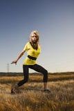 Donna in una posa di ballo in un campo di erba Immagine Stock