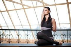 Donna in una posa di pratica del fronte o di gomukhasana della mucca di yoga della tuta scura sul piano d'appoggio davanti alle g Immagine Stock Libera da Diritti