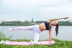 Donna in una posa di yoga con le sue spese generali di raggiungimento del braccio che sollevano gamba Immagine Stock
