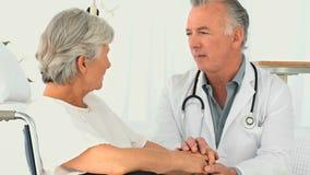 Donna in una sedia a rotelle che parla con suo medico stock footage