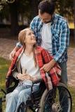Donna in una sedia a rotelle nel parco con un uomo L'uomo ha coperto le sue spalle di plaid del plaid Immagini Stock