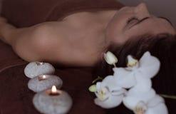 Donna in una stazione termale su un fondo dei fiori e delle candele Salute e pelle e capelli di bellezza immagini stock