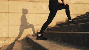 Donna in una tuta sportiva nera che flette i muscoli della coscia interna nell'addestramento La ragazza allunga prima i muscoli d
