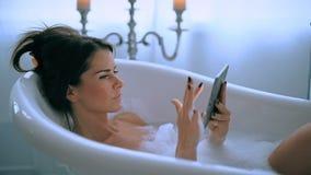 Donna in una vasca da bagno stock footage