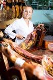 Donna in uniforme che affetta la carne deliziosa di prosciutto di Parma Fotografia Stock Libera da Diritti