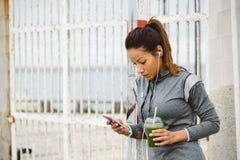 Donna urbana di forma fisica che manda un sms sul suo smarphone Fotografia Stock