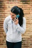 Donna urbana di forma fisica sul sorridere di chiamata dello smartphone Fotografia Stock