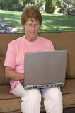 donna usando maggiore del computer portatile del calcolatore fotografia stock