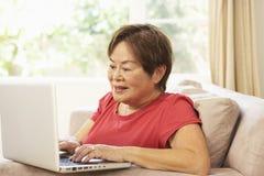 donna usando maggiore del computer portatile domestico Fotografia Stock