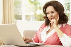 donna usando maggiore del computer portatile domestico Fotografia Stock Libera da Diritti