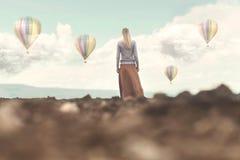 Donna vaga che esamina le mongolfiere che scendono fotografie stock libere da diritti