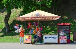 Donna-venditore in parco al contatore con il gelato, palloni Fotografie Stock