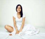 Donna vera castana abbastanza indiana a letto che sorride Fotografia Stock
