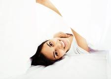 Donna vera castana abbastanza indiana a letto che sorride, strati bianchi Fotografia Stock Libera da Diritti