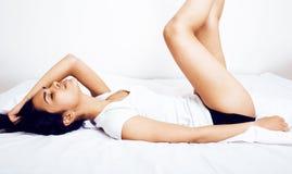Donna vera castana abbastanza indiana a letto che sorride, strati bianchi, Immagini Stock