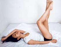 Donna vera castana abbastanza indiana a letto che sorride, strati bianchi, fine della pelle del tann sul mulatto Non può dormire Immagini Stock