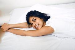 Donna vera castana abbastanza indiana a letto che sorride, strati bianchi, fine della pelle del tann sul mulatto Non può dormire Fotografia Stock Libera da Diritti