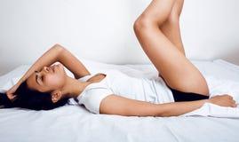 Donna vera castana abbastanza indiana a letto che sorride, strati bianchi, fine della pelle del tann sul mulatto Non può dormire Fotografia Stock