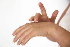 Donna vera che sfrega le sue mani con la lozione del mistouriser contro un fondo bianco Immagine Stock Libera da Diritti
