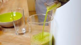 Donna verde del frullato che produce i frullati di verdure con il miscelatore archivi video