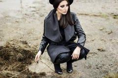 Donna vestita in cappotto e black hat Fotografie Stock Libere da Diritti