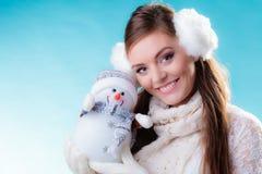 Donna in vestiti caldi che tengono il giocattolo del pupazzo di neve Fotografie Stock
