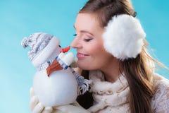 Donna in vestiti caldi che tengono il giocattolo del pupazzo di neve Immagini Stock
