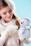 Donna in vestiti caldi che tengono il giocattolo del pupazzo di neve Fotografia Stock Libera da Diritti