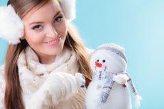 Donna in vestiti caldi che tengono il giocattolo del pupazzo di neve Fotografia Stock