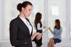 Donna in vestiti convenzionali che legge informazioni dalla compressa Immagini Stock
