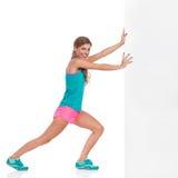 Donna in vestiti di sport che spingono muro di cinta Immagine Stock