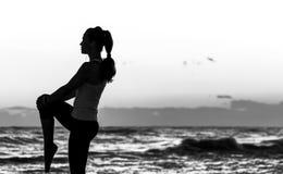 Donna in vestiti di sport sull'allungamento della spiaggia Siluetta Fotografia Stock