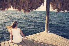 Donna in vestito bianco che esamina oceano fotografia stock libera da diritti