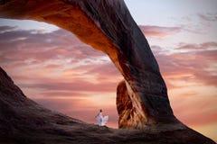 Donna in vestito bianco che medita sotto l'arco naturale dell'arenaria all'alba fotografia stock libera da diritti