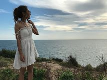Donna in vestito bianco sulla montagna che guarda al mare con il tramonto ed il cielo blu fotografie stock libere da diritti