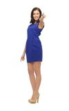 Donna in vestito blu che indica il suo dito Immagine Stock