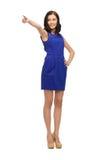 Donna in vestito blu che indica il suo dito Fotografie Stock Libere da Diritti