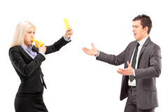 Donna in vestito che mostra un cartellino giallo e che soffia un whist Fotografie Stock Libere da Diritti