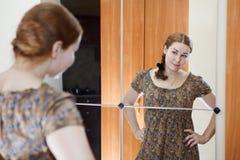 Donna in vestito che si leva in piedi contro lo specchio Fotografie Stock