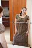 Donna in vestito che si leva in piedi contro lo specchio Immagini Stock
