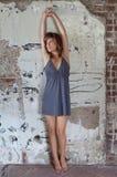 Donna in vestito contro la parete immagine stock