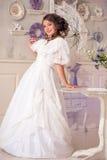 Donna in vestito d'annata di lusso che sta nella stanza luminosa Immagini Stock
