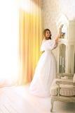 Donna in vestito d'annata di lusso che sta nella stanza luminosa Fotografie Stock Libere da Diritti